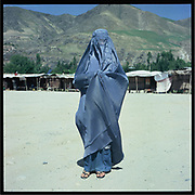 A woman wearing blue jeans stands on the dirt road in Badakshan.