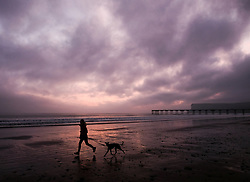 © Licensed to London News Pictures. <br /> 27/03/20167. <br /> Saltburn by the Sea, UK.  <br /> <br /> A woman runs with her dog along the beach as fog build along the coast in Saltburn by the Sea.<br /> <br /> Photo credit: Ian Forsyth/LNP