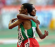 Kenenisa Bekele of Ethiopia embraces countryman Haile Gebrselassie after they finished first and secondin the IAAF World Championships in Athletics at Stade de France on Sunday, Aug, 24, 2003.
