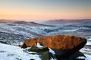 Dawn light picks out a gritstone boulder at Stanage Edge, looking out towards a distant Over Owler Tor and Millstone Edge. A snowy winter scene in the Derbyshire Peak District, England, UK.