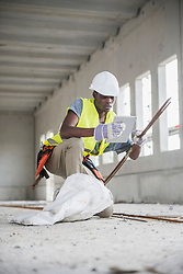 Construction worker holding digital tablet and iron bars at building site, Munich, Bavaria, Germany