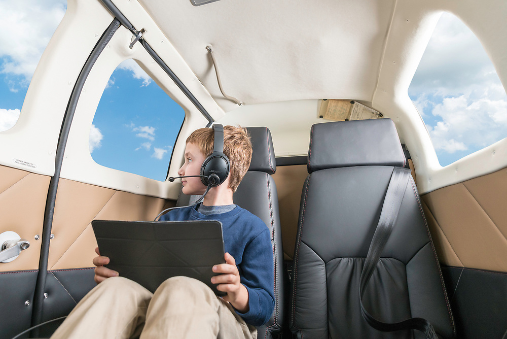 Young boy enjoys the view in a jet holding his iPad and wearing the Bose QC35 with the Nflightmic attached. Nflightmic lifestyle photo shoot created by Arkansas based commercial photographer, Alex Kent