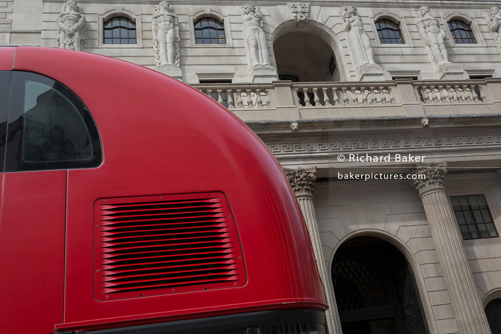 """The rear curvature of a London Routemaster bus and the exterior of the Bank of England on Threadneedle Street in the City of London - the capital's financial district, on 3rd September 2018, in London England. The Bank of England, is the central bank of the United Kingdom and the model on which most modern central banks have been based. Established in 1694, it is the second oldest central bank in the world. Sir Herbert Baker's rebuilding of the Bank, demolishing most of Sir John Soane's earlier building, was described by architectural historian Nikolaus Pevsner as """"the greatest architectural crime, in the City of London, of the twentieth century""""."""