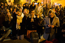 People and catholics pray and cry and sing for the Notre Dame Cathedral. Bystanders look on as flames and smoke are seen billowing from the roof at Notre-Dame Cathedral in Paris on April 15, 2019. A fire broke out at the landmark Notre-Dame Cathedral in central Paris, potentially involving renovation works being carried out at the site, the fire service said.Images posted on social media showed flames and huge clouds of smoke billowing above the roof of the gothic cathedral, the most visited historic monument in Europe. Photo by Raphael Lafargue/ABACAPRESS.COM