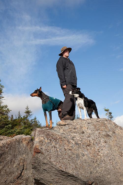 Hiker with Australian Shepherd and Doberman on mountaintop