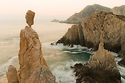 A balanced rock sculpture is perched precariously over a rocky coastline while waves crash into the sea stacks at sunset in Maruata Bay, Michoacan State, Mexico. Maruata is a Pomaro fishing village set in a beautiful bay and a popular destination among independent-minded travelers.