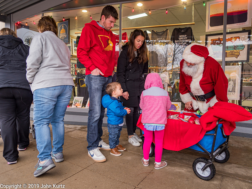 "30 NOVEMBER 2019 - WEST DES MOINES, IOWA: SANTA CLAUS talks to members of the Wilson family on 5th Street, the main business street in West Des Moines, Saturday. The Wilsons are visiting Des Moines from Arlington Heights, Illinois. Santa was handing out gifts to children on Small Business Saturday. ""Small Business Saturday"" was first observed in the United States on November 27, 2010, as a counterpart to Black Friday and Cyber Monday, which are generally considered events at malls, ""big box"" stores and e-commerce retailers. Small Business Saturday encourages holiday shoppers to patronize brick and mortar businesses that are small and local. Small Business Saturday is a registered trademark of American Express.       PHOTO BY JACK KURTZ"
