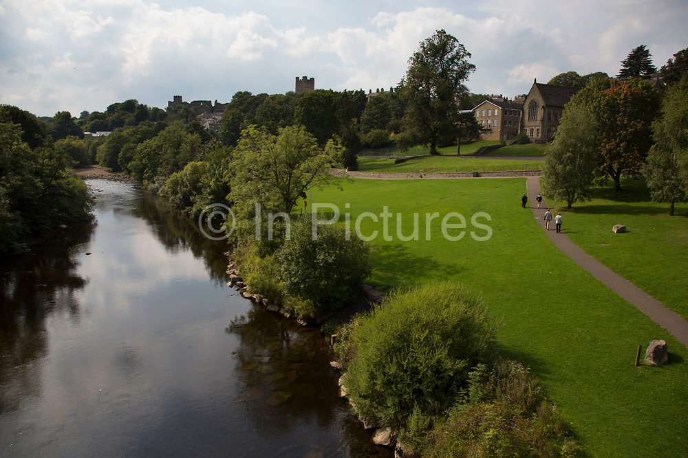 Park looking north along the River Swale towards Richmond Castle. Richmond is a market town and the centre of the district of Richmondshire. Historically in the North Riding of Yorkshire, it is situated on the edge of the Yorkshire Dales National Park. North Yorkshire, England, UK.