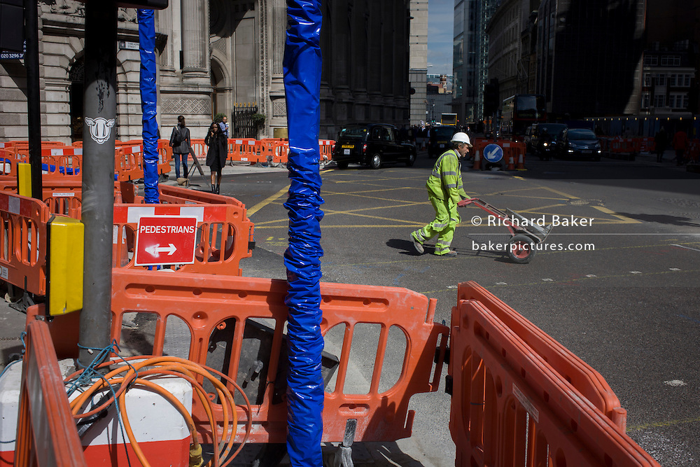 A construction workman pushes a trolley across Bishopsgate (Street) in the City of London, the capital's financial district.