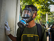 26 DECEMBER 2013 - BANGKOK, THAILAND: An anti-government protestor with a gas mask watches riot police in the Thai Japan Stadium. Thousands of anti-government protestors flooded into the area around the Thai Japan Stadium to try to prevent the drawing of ballot list numbers by the Election Commission, which determines the order in which candidates appear on the ballot of the Feb. 2 election. They were unable to break into the stadium and ballot list draw went as scheduled. The protestors then started throwing rocks and small explosives at police who responded with tear gas and rubber bullets. At least 20 people were hospitalized in the melee and one policeman was reportedly shot by anti-government protestors.      PHOTO BY JACK KURTZ