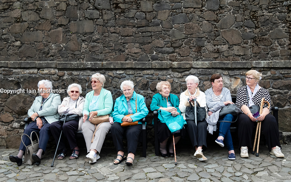 Group of senior women sitting on bench at Stirling Castle in Scotland, UK