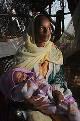 """Tiblits neighbor Zaid Tesheme, 31 holds her baby after he was baptized with the name Mihreteab inside Coptic St. Mary's chapel in the village of Fithi which means """"justice"""" on the outskirts of  Barentu, Eritrea August 27, 2006. During this ceremony, . The donkey that Tiblets received from the womens union """"Hamade"""", helped them prepare for the celebration afterwards."""