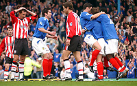 Fotball<br /> FA Barclays Premiership<br /> Portsmouth v Southampton<br /> 24. april 2005<br /> Foto: Digitalsport<br /> NORWAY ONLY<br /> Portsmouth's players mob second goal scorer Arjan De Zeeuw while  Southampton's players look on gutted.