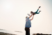 Father lifts daughter in the air at the beach.