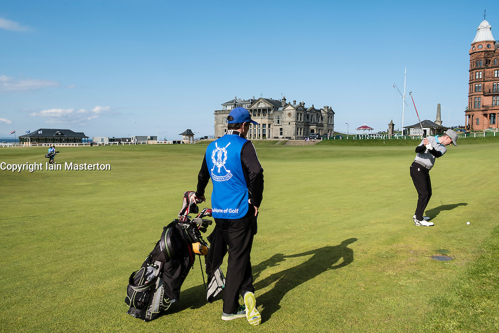 Golfer with caddie playing to 18th green on Old Course at St Andrews in Fife, Scotland, united Kingdom