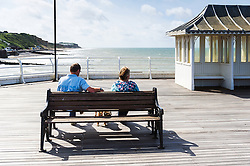 A couple sitting on a bench on Cromer Pier in Norfolk.