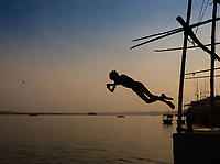 Varanasi, INDIA - CIRCA NOVEMBER 2018: Young kids jumping in the Ganges River in Varanasi. Varanasi is the spiritual capital of India, the holiest of the seven sacred cities and with that one the most frequented places for Sadhus.