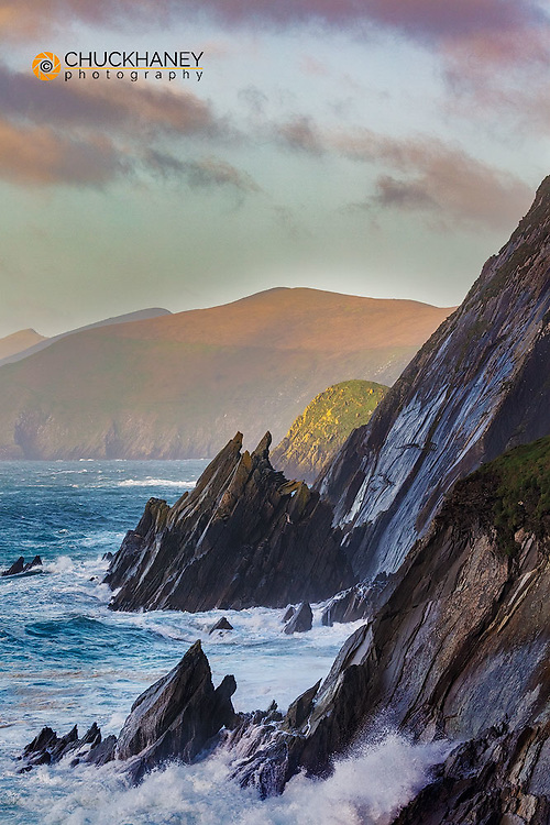 Waves crash into cliffs on Dumore Head with Blasket Islands on the Dingle Peninsula, Ireland