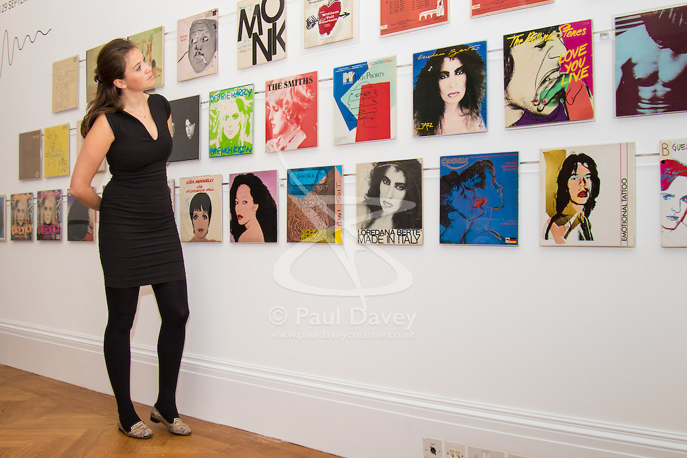 London, September 24th 2015. A member od Sotheby's staff admires the collection of record covers designed by Andy Warhol in the auctioneer's Rock and Pop exhibition running 24th - 28th September ahead of an auction on September 29th. The exhibition gathers together lyrics, instruments, stage costumes and artworks from some of the world's greatest pop and rock performers and groups, including Abba, The Beatles, Bob Dylan, Pink Floyd and Bruce Springsteen.