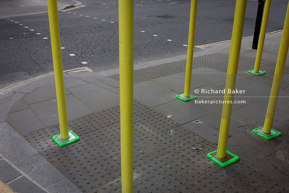 A theme of squares at the foot of scaffolding tubes and pedestrian crossing markings on the road surface, on 9th December 2016, in the City of London.