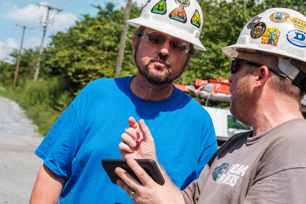 Dwayne Mace, Regional Digital Technician, from Lamar Advertising Company, left, and Robert Farthing, Operations Manager discuss progress as technicians were installing a digital billboard structure along Wards Road in Lynchburg, VA Wednesday, August 29, 2018. U.S. companies are investing in re-training efforts to fill a slew of open positions as a tight labor market and changing job requirements makes it hard to find qualified staffers.<br /> CREDIT: Justin Ide for The Wall Street Journal<br /> RETRAIN