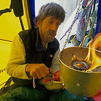 BAFFIN ISLAND, NUNAVUT, CANADA. John Catto risks a dangerous flare-up while lighting a hanging stove in Portaledge camp, high on Great Sail Peak.
