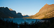 """Sunrise light hits Going-to-the-Sun Mountain and Little Chief Mountain in the Lewis Range above Saint Mary Lake (4484 feet / 1367 meters elevation) in Glacier National Park, Montana, USA. The Going-to-the-Sun Road runs along the north shore. Here the great plains end and the Rocky Mountains abruptly rise 5000 feet above the lake. Since 1932, Canada and USA have shared Waterton-Glacier International Peace Park, which UNESCO declared a World Heritage Site (1995) containing two Biosphere Reserves (1976). Rocks in the park are primarily sedimentary layers deposited in shallow seas over 1.6 billion to 800 million years ago. During the tectonic formation of the Rocky Mountains 170 million years ago, the Lewis Overthrust displaced these old rocks over newer Cretaceous age rocks. Glaciers carved spectacular U-shaped valleys and pyramidal peaks as recently as the Last Glacial Maximum (the last """"Ice Age"""" 25,000 to 13,000 years ago). Of the 150 glaciers existing in the mid 1800s, only 25 active glaciers remain in the park as of 2010, and all may disappear by 2020, say climate scientists. (Panorama stitched from 2 overlapping images.)"""