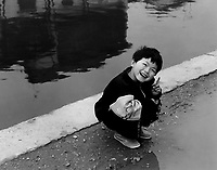 A little boy smiles as he makes a number one sign with his hands in a watertown near Shanghai.