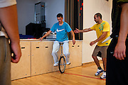 Inmates are trying to use a one-wheeled bicycle inside the prison gym during the time they regularly spend carrying out physical exercise and learning about the human body at the luxurious Halden Fengsel, (prison) near Oslo, Norway.