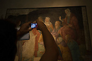 Tourist uses camera to record details of a medieval fresco by the Italian artist Alessandro di Mariano di Vanni Filipepi, better known as Sandro Botticelli.