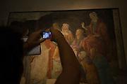 Tourist uses camera to record details of a medieval fresco by the Italian artist Alessandro di Mariano di Vanni Filipepi, better known as Sandro Botticelli.