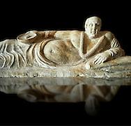 Close up of an Etruscan Hellenistic style cinerary, funreary, urn cover with a man,  National Archaeological Museum Florence, Italy , black background .<br /> <br /> If you prefer to buy from our ALAMY PHOTO LIBRARY  Collection visit : https://www.alamy.com/portfolio/paul-williams-funkystock - Scroll down and type - Etruscan Florence - into LOWER search box. (TIP - Refine search by adding a background colour as well).<br /> <br /> Visit our ETRUSCAN PHOTO COLLECTIONS for more photos to download or buy as wall art prints https://funkystock.photoshelter.com/gallery-collection/Pictures-Images-of-Etruscan-Historic-Sites-Art-Artefacts-Antiquities/C0000GgxRXWVMLyc