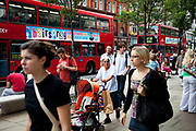 Shoppers and buses on Oxford Street in Central London. This is a busy shopping area full of all the main high street chain stores.