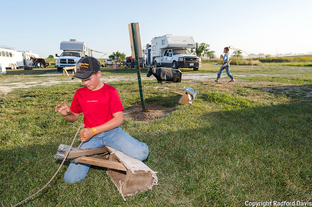 Jaxson, in foreground, practices his calf roping on a wooden dummy while his brother  Dawson practices roping a dummy calf in the background. The trailer park is filled with kids and family and horses and trucks coming and going. Jaxson's ties are very quick.