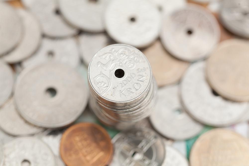 Norsk kronestykke på toppen av en myntstabel omgitt av norsk mynt. Selektiv fokus.