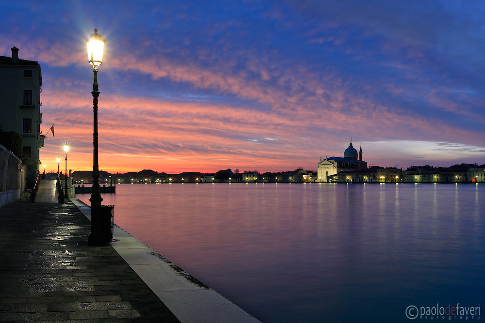 Some wonderful stripes of red clouds announcing a glorious sunrise over the Giudecca Canal in Venice, Italy.Taken on a very early morning at the beginning of December about 30 minutes before dawn, this is stitched from six vertical frames.