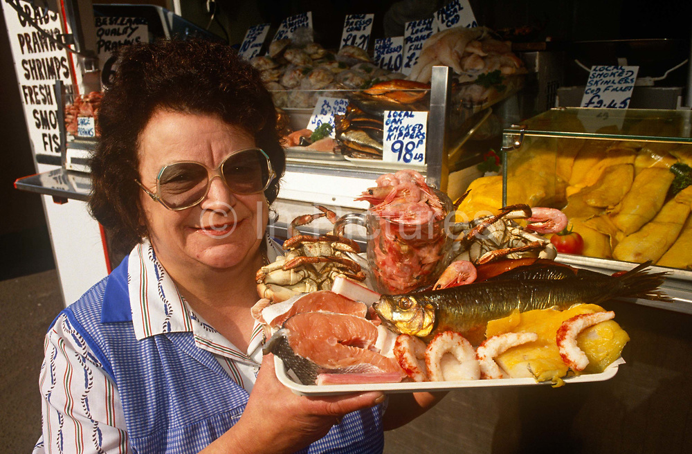 A portrait of a lady fishmonger and her shellfish in the Norfolk seaside town of Great Yarmouth. Holding up a tray of fish and shellfish, the lady proudly stands outside her kiosk in the centre of this eastern England seaside resort. A pot of shrimps, some crabs, salmon steaks and traditional kippers are shown to us. In the background are cod fillets, prawns and other smoked fish.
