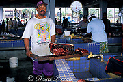 butcher chops up meat from blackfish or shortfin pilot whale, Globicephala macrorhynchus, at Kingston Fish Market, St. Vincent, West Indies, Saint Vincent and the Grenadines ( Caribbean )