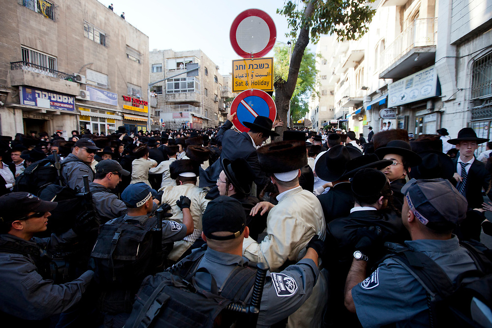 Israeli policemen scuffle with ultra-Orthodox protesters as they attempt to block Neviim Street, a central thoroughfare in Jerusalem, on July 16, 2011. Close to a thousand ultra-Orthodox Jewish men held a demonstration against the desecration of Shabbat, marking one hundred weekends to the opening of the Karta municipal parking lot in the capital.