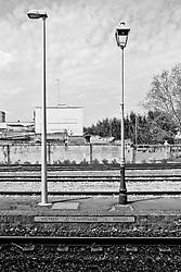 Due lampioni affiancati sulla banchina di un binario nella stazione delle ferrovie SUD EST   di Galatina; testimoniano il passaggio dal periodo storico dell'immediato dopoguerra ai giorni nostri. In basso si nota il segnale di divieto di attraversamento binari.  Reportage che racconta le situazioni che si incontrano durante un viaggio lungo le linee ferroviarie SUD EST nel salento.