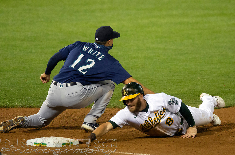 Sep 25, 2020; Oakland, California, USA; Seattle Mariners first baseman Evan White (12) applies the tag to pick off Oakland Athletics Robbie Grossman (8) during the seventh inning of a Major League Baseball game at Oakland Coliseum. Mandatory Credit: D. Ross Cameron-USA TODAY Sports