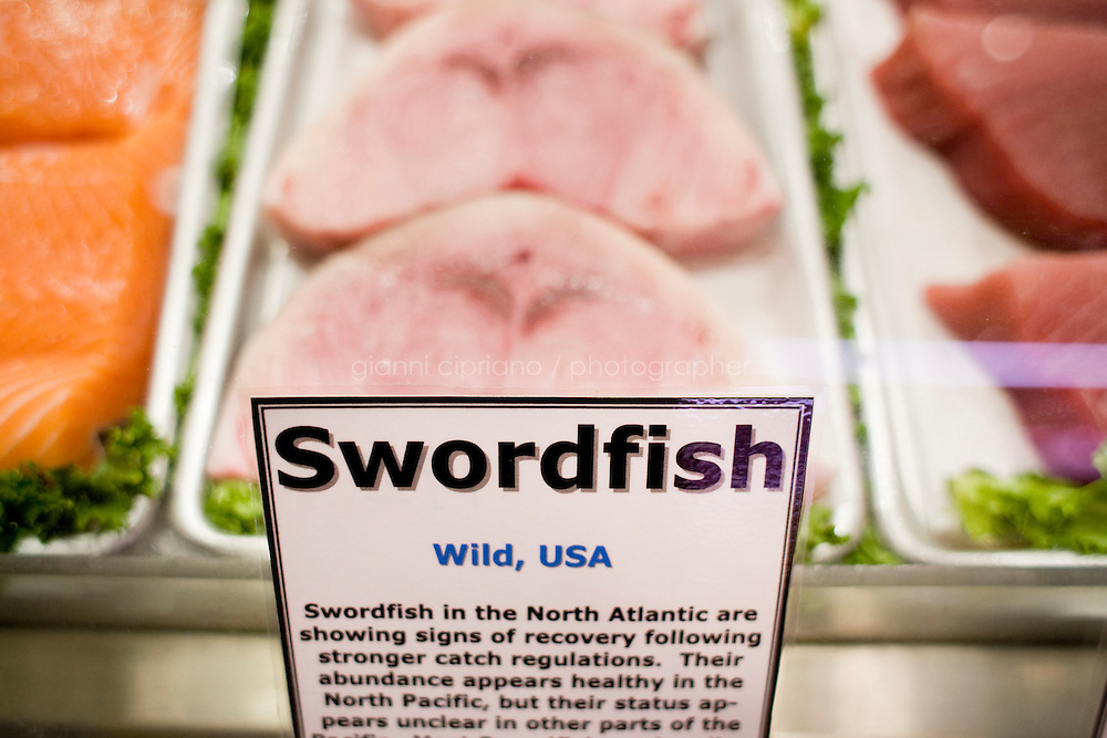"""2 October, 2008. New York, NY. A Country of Origin Label (COOL) for swordfish is here on display at The Wild Edibles fish stand at the Grand Central Market. The signs and symbols on the labels also indicate the sustainability of the seafood. Wild Edibles came up with the idea 2 years ago and implemented it last year, though the COOL is not mandatory for them, since the total amount of their invoicing does not require it. """"We do it because this way people are more aware of where the food they purchase comes from"""", says Steve Schafel, director of retail operations. """"We do it as a service for our customers"""".<br /> <br /> ©2008 Gianni Cipriano for The New York Times<br /> cell. +1 646 465 2168 (USA)<br /> cell. +1 328 567 7923 (Italy)<br /> gianni@giannicipriano.com<br /> www.giannicipriano.com"""