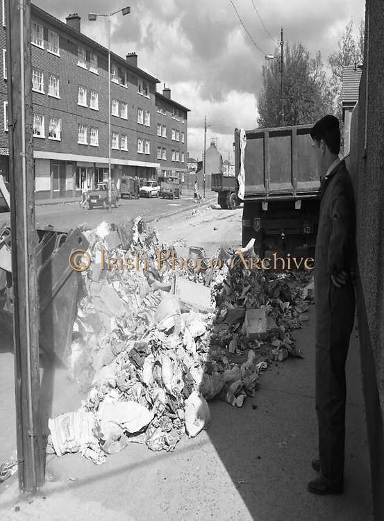 Army Removes Refuse In Dublin..1986..05.06.1986..06.05.1986..5th June 1986..Due to the ongoing strike by Dublin Corporation workers,the army were called in to help clear some of the mounds of rubbish stacking up around the city. Health worries from the rotting rubbish and the danger of rat infestation caused the intervention. The 2nd Garrison Supply and Transport Company,McKee Barracks,Dublin were delegated to clear the rubbish from St Theresa's Flats,Donore Avenue,Dublin...Image of soldier taking a break as the bulldozer seriously reduces the mound of rubbish which had built up within the flats complex.