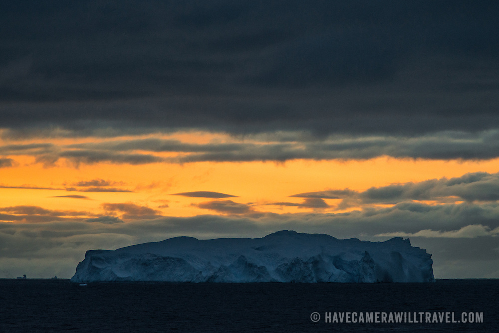 A large iceberg is silhouetted against the orange glow in the sky after sunset near Trinity Islands on the Antarctic Peninsula.