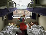 Early sleepers in between Guangzhou and Shaoguan. Life in the sleeping compartments in the train from Hong Kong to Urumqi, Xinjiang.