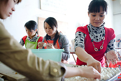 Chinese owner from Guangxi province, right, employs local women to make dumplings at Chinese restaurant near the Haiphong Thermal Power Plant construction site in Trung Son, Vietnam, Nov. 22, 2009. At the construction site here, a few miles northeast of the port city of Haiphong, an entire Chinese world has sprung up, including four walled dormitory compounds for the Chinese workers, restaurants with Chinese signs advertising dumplings and fried rice, and currency exchange shops.