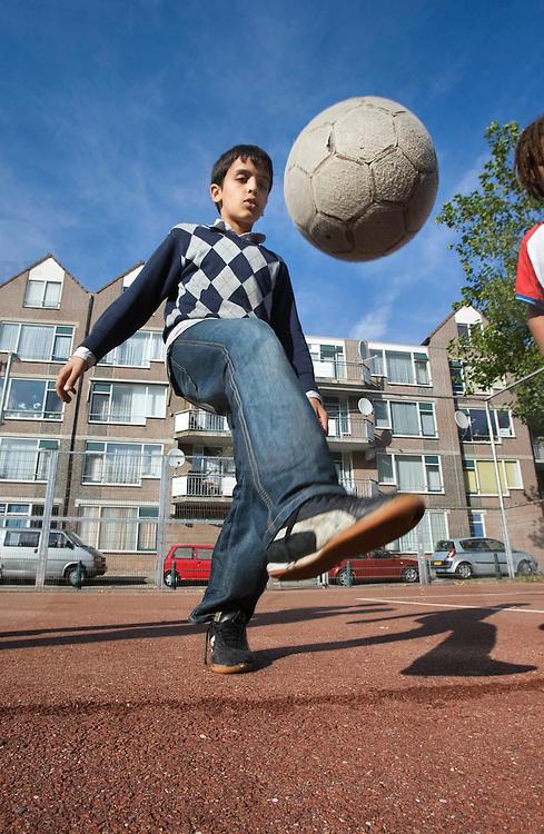 Nederland Rotterdam 01-10-2009 20091001 Foto: David Rozing Achterstandswijk Crooswijk. Allochtone jongen speelt op voetbalveldje, houdt een balletje hoog. Boy playing soccer in Crooswijk, deprived area in Rotterdam, nieghbourhood.                                                       .Foto: David Rozing