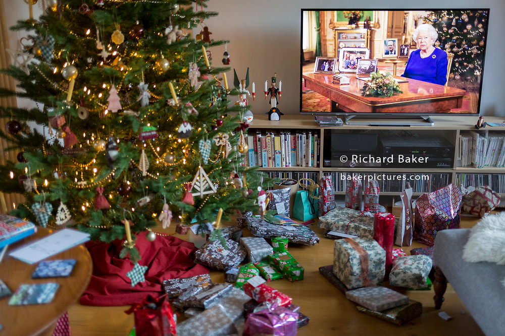 Christmas presents remain unopened beneath a Christmas tree during the Queen's speech to the nation on Christmas Day, a tradition started in 1932 and which she first broadcast on television in 1957, on 25th December 2019, in Bristol, England.