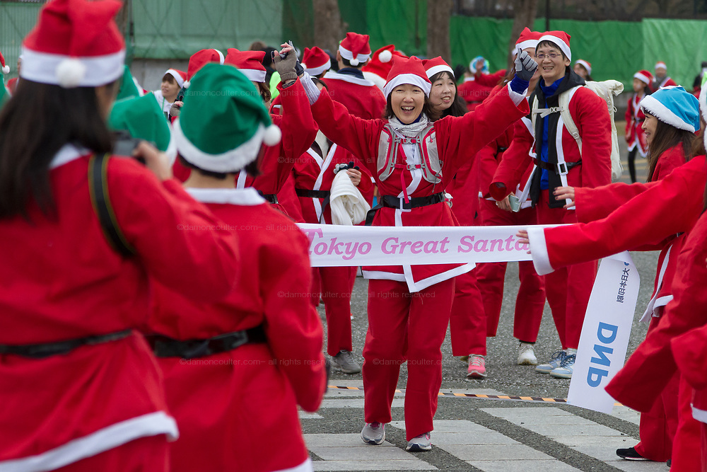 Participants cross the finishing-line after taking part in the Tokyo Great Santa Run in Komazawa-daigaku Olympic Park, Tokyo, Japan. Sunday December 22nd 2019, The great Santa Run was first run in Tokyo in 2018. This years run saw over 3,000 people in Santa costumes run and walk a 4.3 kilometre course to raise money for medical charities in japan and water projects for the Maasai in Kenya.