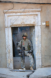 Sgt. Matt Smith, of the 1st Infantry, 17th Regiment, helps Iraqi forces patrol western Mosul, Iraq, Dec. 14, 2005. This is part of an effort to provide security in preparation for Iraq's first post-Saddam parliamentary elections. The western sector is home to Mosul's primarily Sunni population, which has been resistant to the American presence in Iraq.